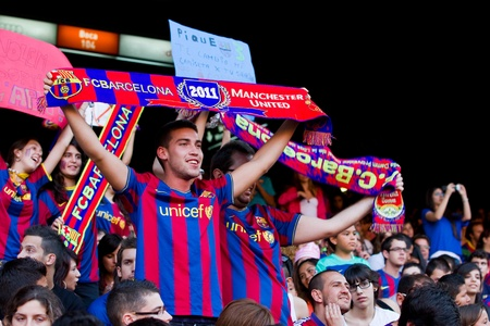 BARCELONA, SPAIN - MAY 13, 2011: Unidentified FC Barcelona supporters celebrate the Spanish League Championship victory in Camp Nou stadium. Stock Photo - 11652843