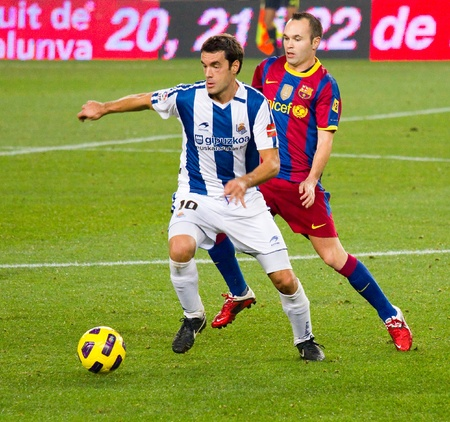 iniesta: BARCELONA, SPAIN - DECEMBER 13, 2010: Andres Iniesta (R) in action during the Spanish Soccer League match between FC Barcelona and Real Sociedad, final score 5 - 0, in Camp Nou stadium.