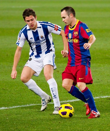 BARCELONA, SPAIN - DECEMBER 13, 2010: Andres Iniesta (R) in action during the Spanish Soccer League match between FC Barcelona and Real Sociedad, final score 5 - 0, in Camp Nou stadium.