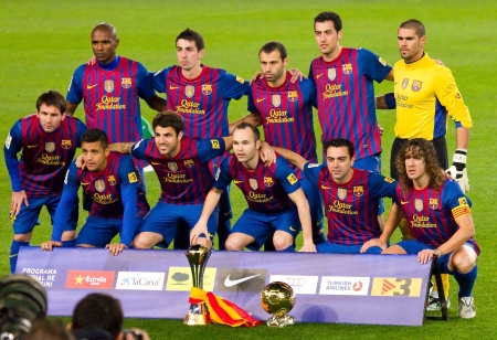 BARCELONA - JANUARY 15, 2012: FC Barcelona team offers the FIFA Club World Cup (L) and FIFA World Player Gold Ball Trophy to supporters, in Camp Nou stadium. Stock Photo - 12058611