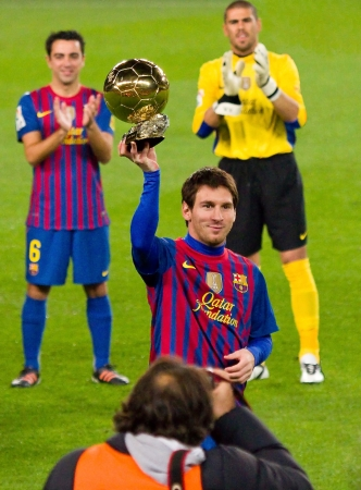 BARCELONA, SPAIN - JANUARY 15, 2012: Lionel Messi shows his third FIFA World Player Gold Ball Award to the soccer supporters of Football Club Barcelona, on January 15, 2012 in Nou Camp stadium.