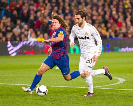 BARCELONA - JANUARY 25: Carlos Puyol (L) and Gonzalo Higuain in action during the Spanish Cup match between FC Barcelona and Real Madrid, final score 2 - 2, on January 25, 2012, in Barcelona, Spain.