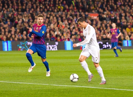 BARCELONA - JANUARY 25: Cristiano Ronaldo (R) and Gerard Pique in action during the Spanish Cup match between FC Barcelona and Real Madrid, final score 2 - 2, on January 25, 2012, in Barcelona, Spain.