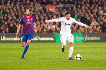 BARCELONA - JANUARY 25: Sergio Busquets (L) and Mesut Ozil in action during the Spanish Cup match between FC Barcelona and Real Madrid, final score 2 - 2, on January 25, 2012, in Barcelona, Spain.