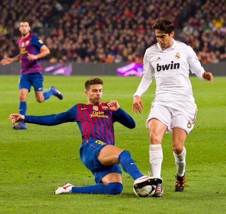 BARCELONA - JANUARY 25: Gerard Pique (L) and Ricardo Kaka in action during the Spanish Cup match between FC Barcelona and Real Madrid, final score 2 - 2, on January 25, 2012, in Barcelona, Spain.