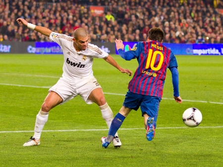 BARCELONA - JANUARY 25: Pepe Laveran (L) and Leo Messi in action during the Spanish Cup match between FC Barcelona and Real Madrid, final score 2 - 2, on January 25, 2012, in Barcelona, Spain. Stock Photo - 12142579