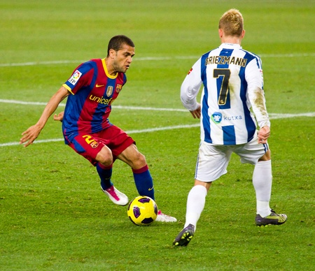 BARCELONA, SPAIN - DECEMBER 13, 2010: Dani Alves (L) in action during the Spanish Soccer League match between FC Barcelona and Real Sociedad, final score 5 - 0, in Camp Nou stadium.