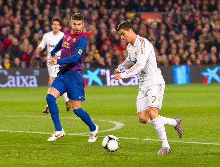 BARCELONA - JANUARY 25: Gerard Pique and Cristiano Ronaldo in action during the Spanish Cup match between FC Barcelona and Real Madrid, final score 2 - 2, on January 25, 2012, in Barcelona, Spain.