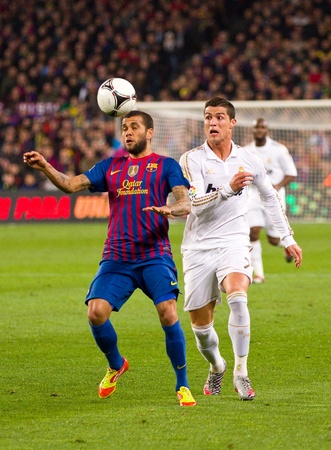 BARCELONA - JANUARY 25: Dani Alves and Cristiano Ronaldo in action during the Spanish Cup match between FC Barcelona and Real Madrid, final score 2 - 2, on January 25, 2012, in Barcelona, Spain.