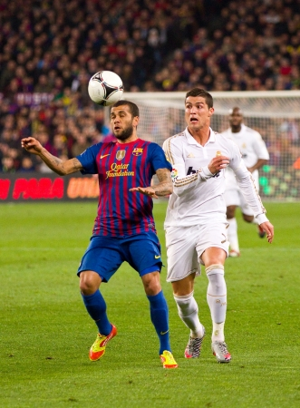 BARCELONA - JANUARY 25: Dani Alves and Cristiano Ronaldo in action during the Spanish Cup match between FC Barcelona and Real Madrid, final score 2 - 2, on January 25, 2012, in Barcelona, Spain Stock Photo - 14755538