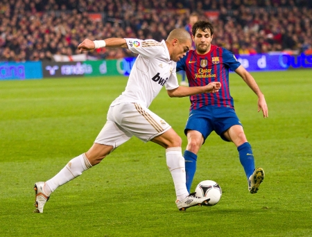 BARCELONA - JANUARY 25: Pepe Laveran and Cesc Fabregas in action during the Spanish Cup match between FC Barcelona and Real Madrid, final score 2 - 2, on January 25, 2012, in Barcelona, Spain Stock Photo - 14755537