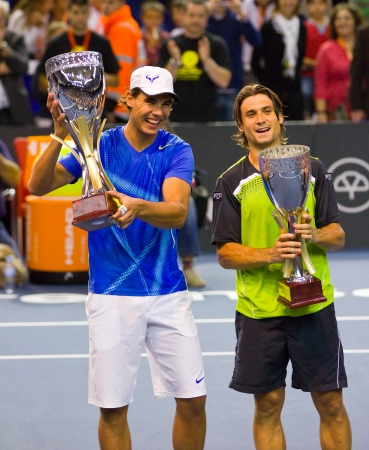 BARCELONA - OCTOBER 22: Rafa Nadal and David Ferrer offering their trophies after a tennis match organized as a tribute to Andreu Gimeno, on October 22, 2011, in Palau Blaugrana, Barcelona, Spain