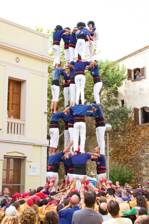 TIANA, SPAIN - SEPTEMBER 18: Unidentified people of Castellers de Mataro team do a Castell or human tower, typical tradition in Catalonia, on September 18, 2011, in Tiana, Barcelona, Spain