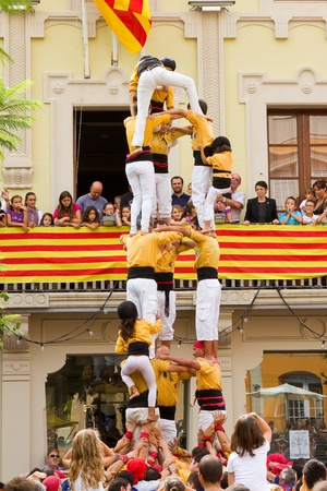 TIANA, SPAIN - SEPTEMBER 18: Unidentified people of Castellers de Badalona team do a Castell or human tower, typical tradition in Catalonia, on September 18, 2011, in Tiana, Barcelona, Spain