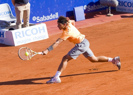 BARCELONA - APRIL 29: Spanish tennis player Rafael Nadal in action during his final match against David Ferrer at Barcelona tennis tournament Conde de Godo on April 29, 2012, in Barcelona, Spain 에디토리얼