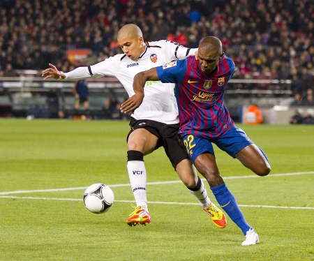 cf: BARCELONA -    Sofiane Feghouli and Eric Abidal in action during the Spanish Cup match between FC Barcelona and Valencia CF, final score 2-0,   in Barcelona, Spain