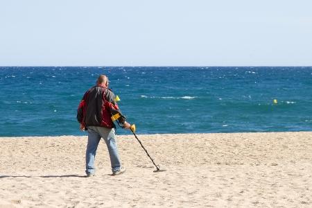 LLORET DE MAR, SPAIN - APRIL 30  Unidentified man looking for lost objects with a metal detector in Lloret de Mar, a famous touristic destination in Mediterranean coast, on April 30, 2012, in Lloret, Spain