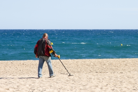 metal detector: LLORET DE MAR, SPAIN - APRIL 30  Unidentified man looking for lost objects with a metal detector in Lloret de Mar, a famous touristic destination in Mediterranean coast, on April 30, 2012, in Lloret, Spain
