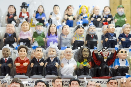 Caganers, originally a character in Catalan mythology, now portraying famous celebrities or characters on sale at Santa Llucia Christmas Fair in Barcelona, Spain
