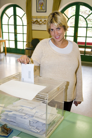polling: Unidentified woman casts his vote at a polling station during European Parliament Election, on May 25, 2014, in El Masnou, Barcelona, Spain