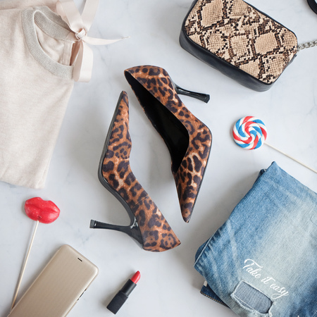 Fashion Lady Clothes Set. Stylish snake Handbag Clutch, trendy leopard shoes, old jeans. Flat lay on white background