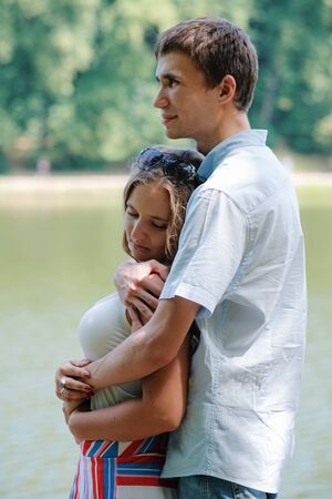 Young loving couple hugging, embracing each other tenderly at beautiful place by the river