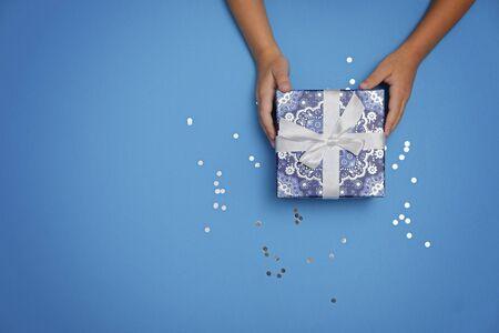 Cadeau in kinderhanden op een blauwe feestelijke achtergrond