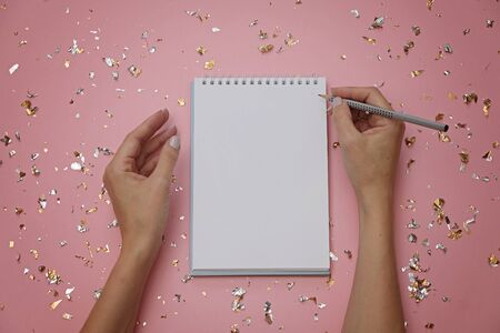 Blank notebook and female hands with pencil on festive pink background