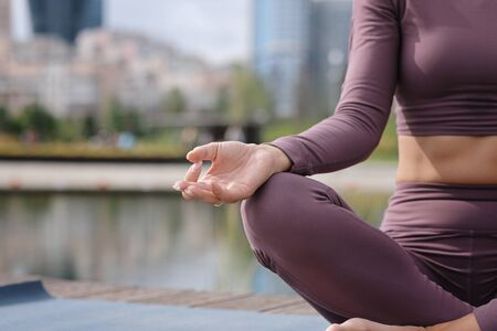 Close up of hands of young office yogi woman sitting on riverbank in the city, meditating with fingers in Jnana mudra