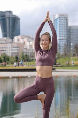 Young woman in tree yoga pose and smiling with city on background.