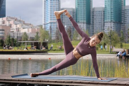 Young woman doing yoga exercises with city on background. Beautiful balance pose