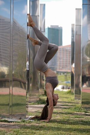 Young woman doing yoga exercises with city on background. Beautiful asana on hands Stockfoto - 129677911