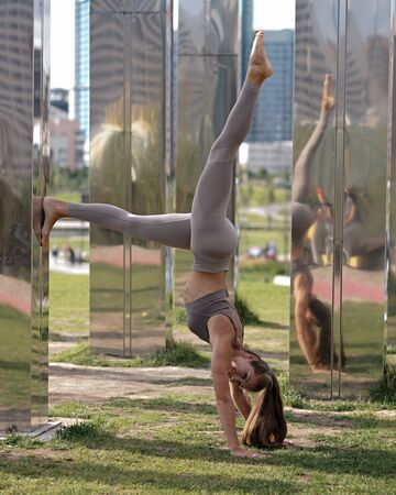 Young woman doing yoga exercises with city on background. Beautiful asana on hands Stockfoto
