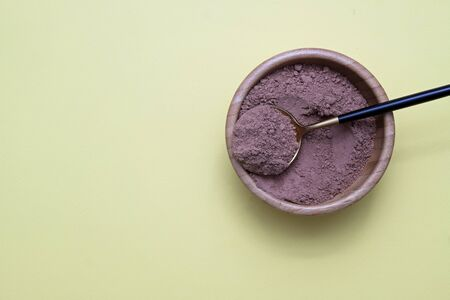 Cocoa powder with a spoon on yellow background.