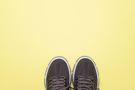 Unbranded modern sporty shoes, sneakers on a yellow background. Top view. Stockfoto
