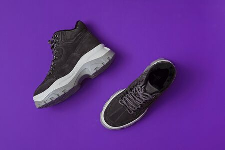 Unbranded modern sporty shoes, sneakers on violet background. Top view.