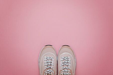 Unbranded modern sporty shoes, sneakers on a pink background. Top view.