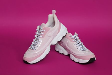 Unbranded modern sporty shoes, sneakers on a pink background.