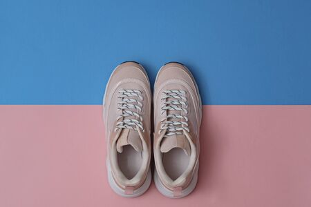 Unbranded modern sporty shoes, sneakers on a pink and blue background. Top view.
