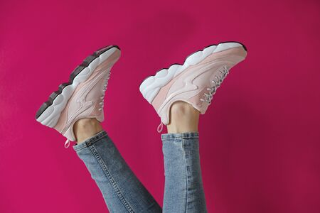 Womans feets in unbranded modern sporty shoes on a pink background.
