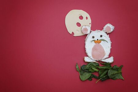 Creative edible christmas rat, mouse food art. Food for kids and festive table. Rat made from bread with cream cheeseon red background.