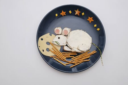 Creative edible christmas rat, mouse food art. Food for kids and festive table. Rat made from bread with cream cheese on a plate Stockfoto