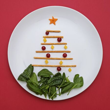 Creative edible christmas tree, food art minimalism. Food for kids and festive table. Tree made from sticks on a plate on red background.