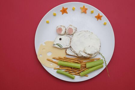 Creative edible christmas rat, mouse food art. Food for kids and festive table. Rat made from bread with cream cheese on a plate on red background. Stockfoto