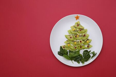 Creative edible vegan christmas tree, food art. Food for kids and festive table. Tree made from kiwi on a plate on red background.