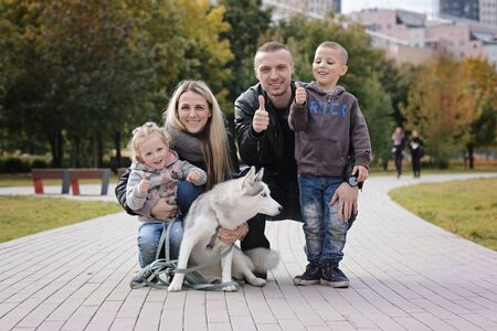 Happy family with little kids and husky dog in the park, autumn outdoors