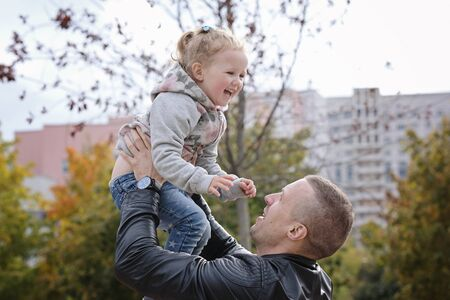 Father playing with his little daughter, throwing her up, having fun. Autumn outdoors Stockfoto
