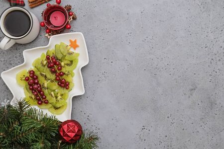 Creative edible vegan christmas tree, food art. Food for kids and festive table. Tree made from kiwi on a white tree plate Stockfoto