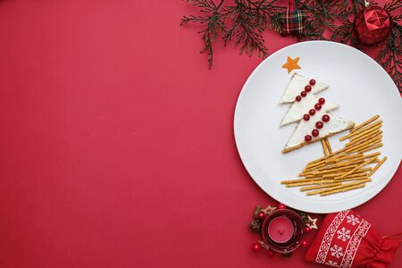 Creative edible christmas tree, food art. Food for kids and festive table. Tree made from bread with cream cheese decorated with berries on a white plate on red background.