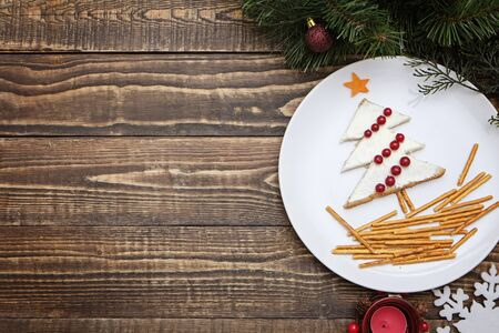 Creative edible christmas tree, food art. Food for kids and festive table. Tree made from bread with cream cheese decorated with berries on a white plate on wooden background.